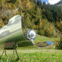 Solární vařič - Pstruh lososovitý na horském slunci v Alpách s čerstvými bylinkami